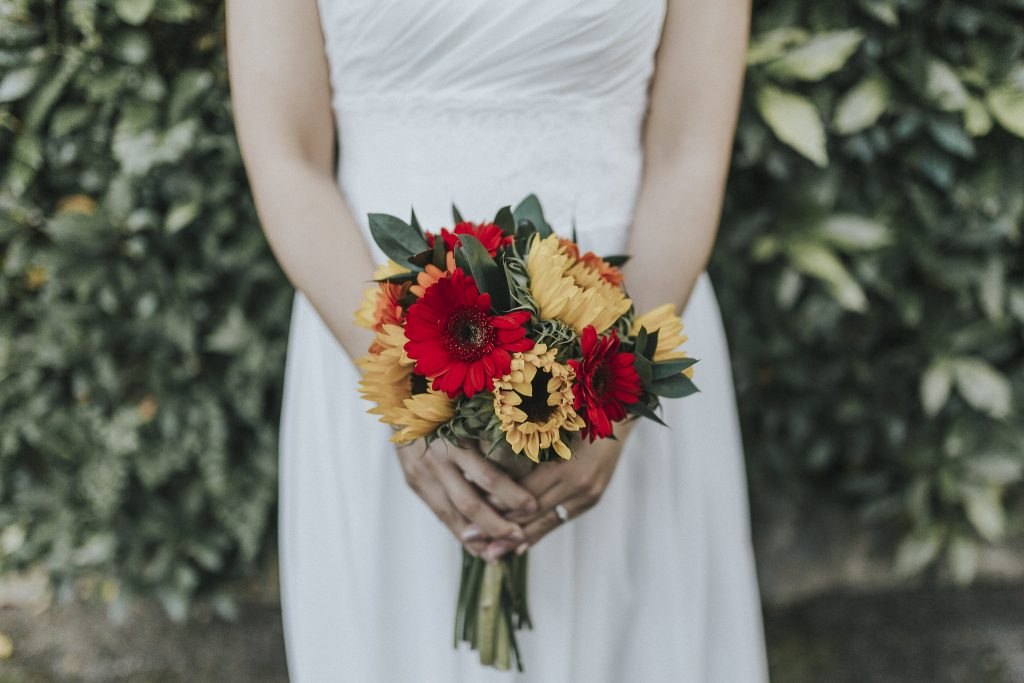 A bride stands with her bouquet at Coltsford Mill on her wedding day in the summer months