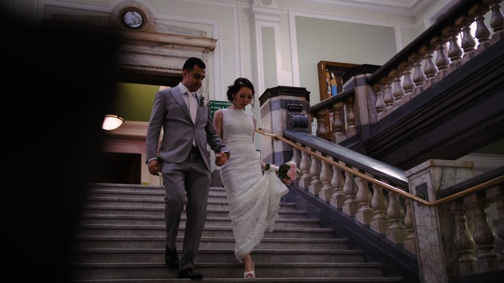 Recently married couple walk down the stairs at Islington town hall