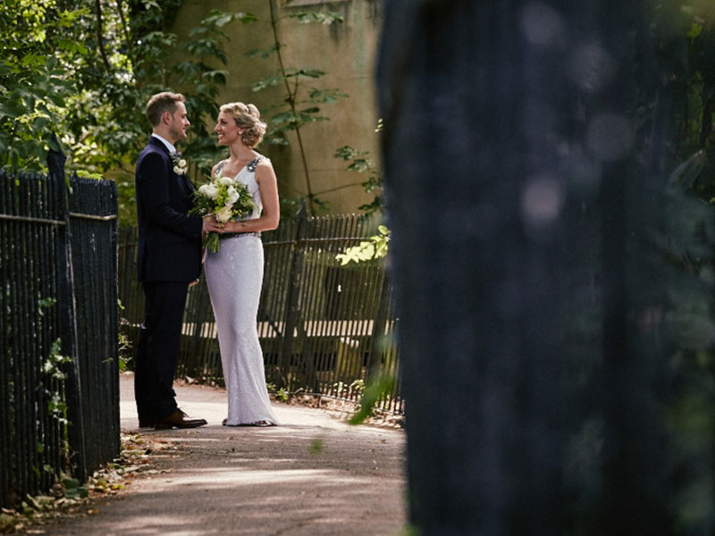 A bride and groom look into each others eyes on a summers day standing on a pathway