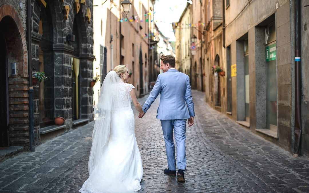 Bride and groom walk down a cobbled street