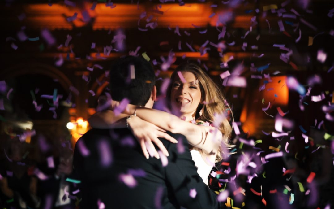 A Bride holds her groom as confetti falls around them