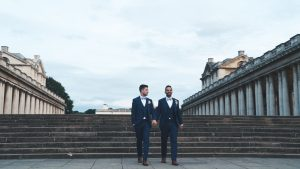 Two grooms walk down the steps of the Old Naval College in Greenwich london