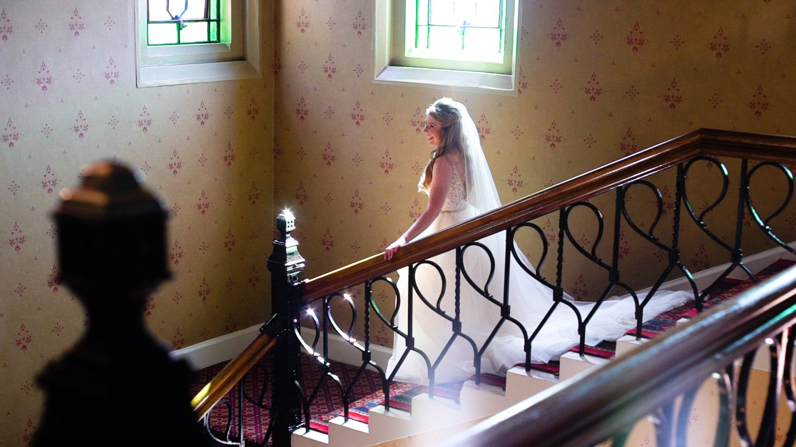A bride walks down a grand staircase with light flooding in
