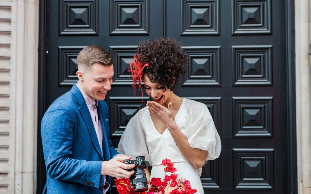 wedding videographer laughs with bride with red hair infront of a large door