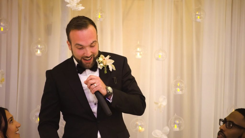 A groom dressed in a tuxedo stands to give his wedding speech