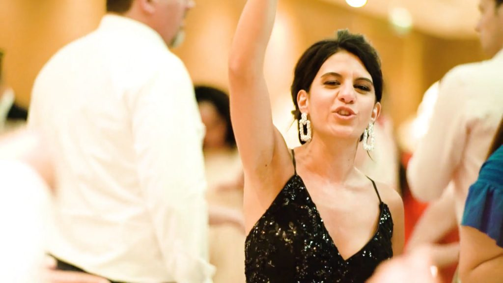 A wedding guest dances with an arm in the air