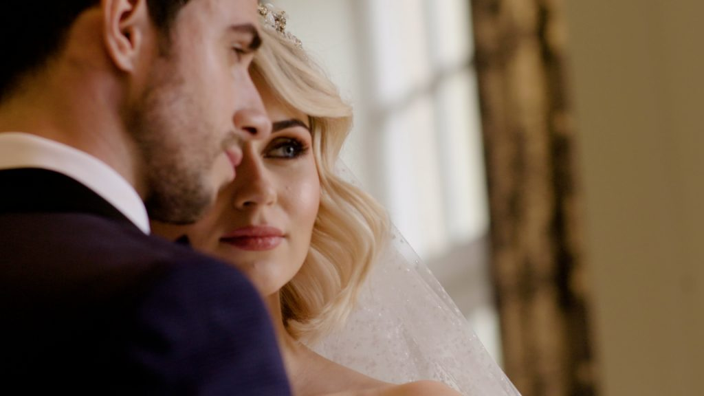 A Jewish bride looks out past her groom infront of a window at a London wedding venue